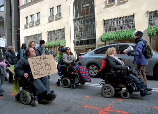Disability-rights activists make themselves heard - and - seen at a protest.